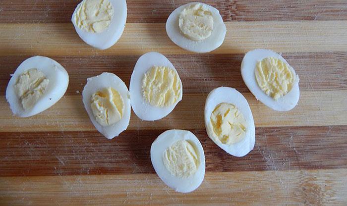 Разрезать обычные и перепелиные яйца пополам